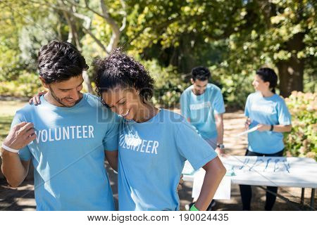 Smiling volunteers talking to each other in the park