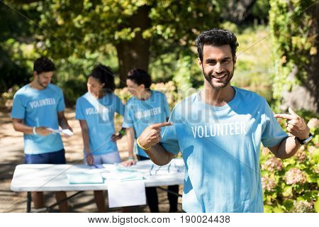 Portrait of smiling volunteer pointing at his t-shirt