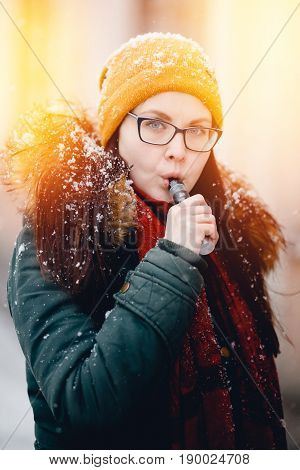 Girl is holding an electronic cigarette in her hand and exhaling steam from her mouth. She is wearing a hat. Winter. Concept smoking in public places. vaping