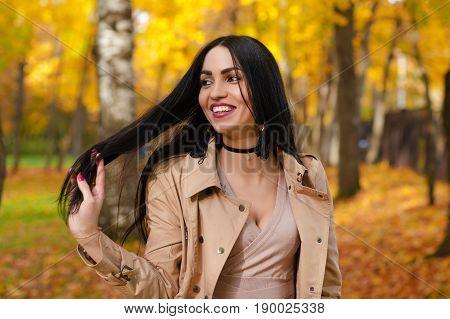 charming smiling brunette on background of autumn park
