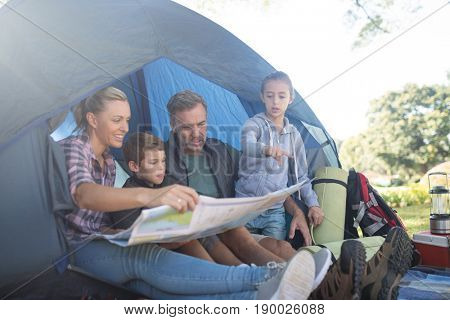 Family reading the map in tent at campsite