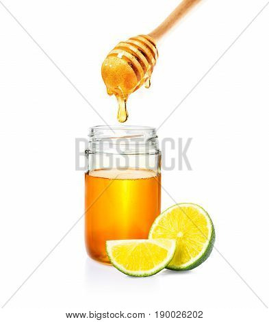honey in glass jar with wooden honey dipper and cut lime on isolated white background