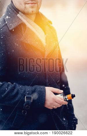 man holds an electronic cigarette in his hand and exhales steam from his mouth. He is wearing a coat. Winter. Concept smoking in public places.