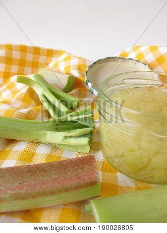 Jar of homemade rhubarb jam and fresh rhubarb