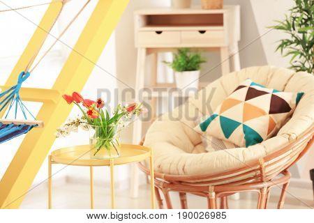 Vase with beautiful flowers on table in modern veranda interior