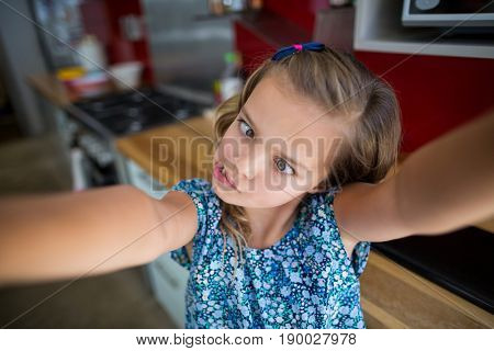 Girl pulling funny faces in kitchen at home