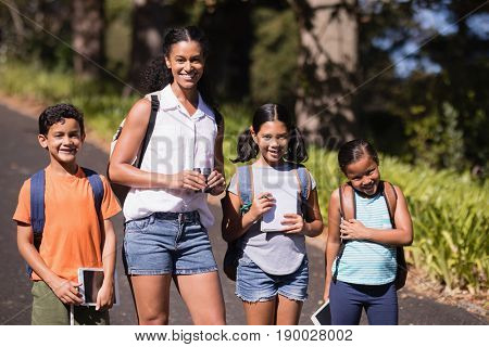 Portrait of students and teacher with digital tablets standing on street during summer field trip