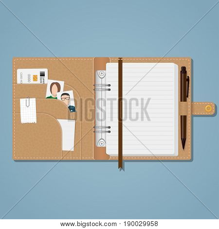 An open brown leather notebook on a rivet with white sheets in a line a bookmark pockets on the cover and a pen holder with a pen. In the cells a credit card a photo of relatives a piece of paper on a paper clip and a small sheet for notes.