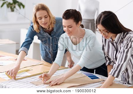 Upsurge of creativity. Two young brunette female tailors tracing patterns on fabrics with pencils while their colleague measuring the width of fabrics