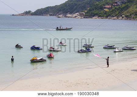 KOH PHANGAN THAILAND - DECEMBER 14 2016: Sea water and jet ski in Haad Rin beach before full moon party. Unidentified people arrived on island Koh Phangan to participate in the Full Moon party