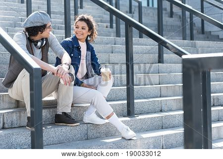 Fun together. Young positive boyfriend and girlfriend are sitting on steps. They are drinking coffee, flirting and looking at each other with joy