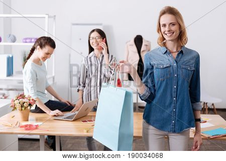Gift waiting for you. Happy smiling woman holding a big blue bag with a gift dress while one colleague talking on the phone and the other working on the laptop