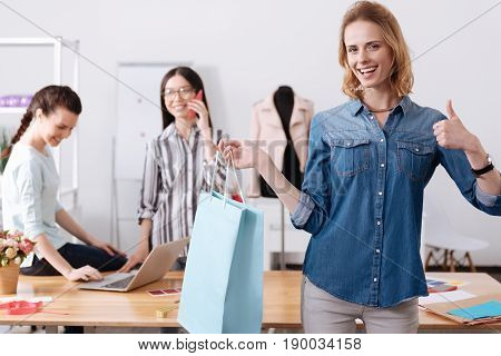 Perfect choice. Charming upbeat woman holding a big blue bag with an item for her customer and showing a thumb up gesture, while her colleagues being busy in the background