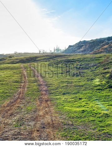 Beautiful landscape - the dirt road running across the field on a background of dramatic clouds