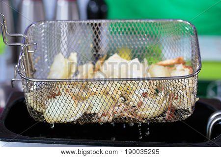 Deep fryer with food on restaurant kitchen