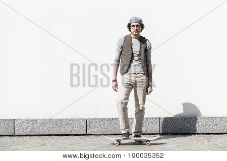 Never give up. Full length portrait of concentrated young guy is getting ready to do trick. He is standing against white wall with one leg is on skateboard. Copy space in the left side