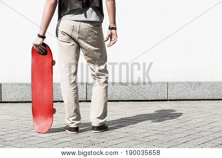 Bright spot. Close-up of legs of young man is standing against white wall and holding red skateboard. Back view. Copy space in the right side