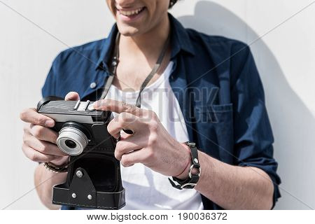 Best photo. Close-up of hands of young man is holding camera and looking at screen with smile. He is standing against white wall