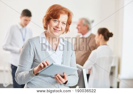 Senior woman using tablet computer at e-learning class