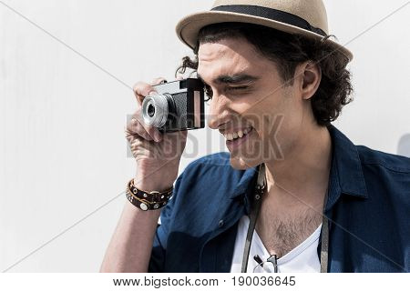 Brightest moments. Joyful positive young photographer is standing in pose of making pictures while holding his camera with smile