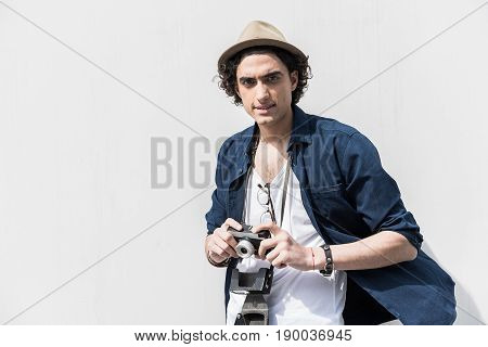 Useful hobby. Portrait of stylish young photographer is standing against white wall and holding his photocamera. He is looking at camera thoughtfully. Copy space in the left side