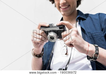 I like it. Close-up low angle of camera which is holding cheerful pleasant guy while looking at screen with smile