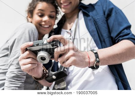 Funny moments. Low angle of positive romantic couple is looking at screen of photocamera with smile. Focus on camera