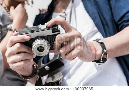 Best memories. Close-up low angle of hands are holding camera. Young couple is looking at screen of photocamera