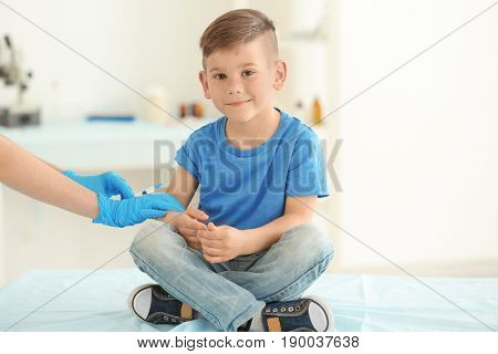Vaccination concept. Female doctor vaccinating cute little boy in clinic
