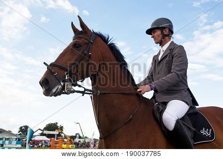 WEEDON, UK - AUGUST 27: A male show jumper prepares his horse at the edge of the ring before starting his round over the jumps at the Bucks County show on August 27, 2015 in Weedon