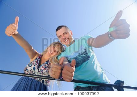Happy young couple with his thump up having fun in nature on blue clear sky background
