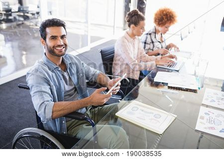 High angle portrait of smiling businessman using digital tablet while sitting on wheelchair at creative office