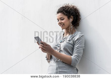 Magic of sound. Cheerful young girl with smartphone is smiling while listening to favorite track through headphone. She is leaning on white wall