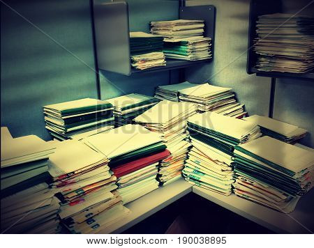 An office cubicle overloaded with stacks of work folders in a dark shadowy corner.