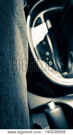 A grey closeup image of a black gearshift console and handbrake next to a driver in jeans.
