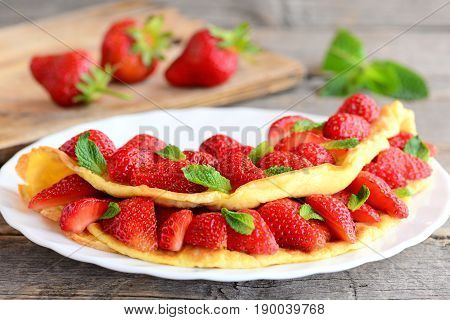 Breakfast souffle omelette with strawberries. Fried omelette filled with fresh strawberries slices and garnished with mint on a plate. Fresh strawberries on old wooden table. Closeup