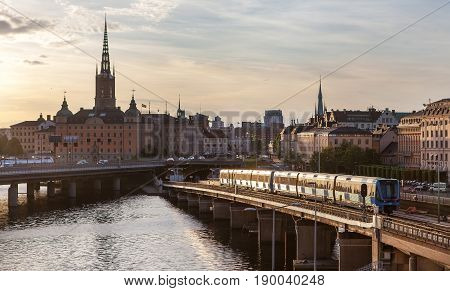 Evening cityscape with subway train crossing the bridge of Gamla Stan Stockholm Sweden
