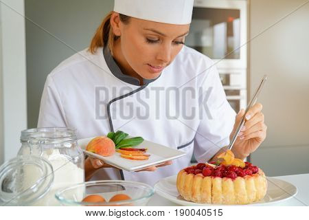 Pastry chef in professional kitchen decorating raspberry cake with fruits