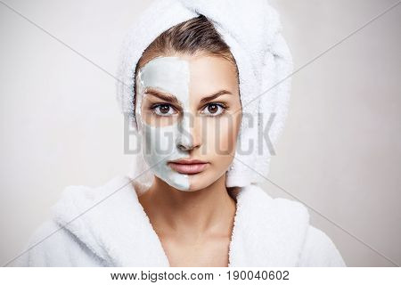 Beautiful woman with mask on her face over gray background. Skincare concept.