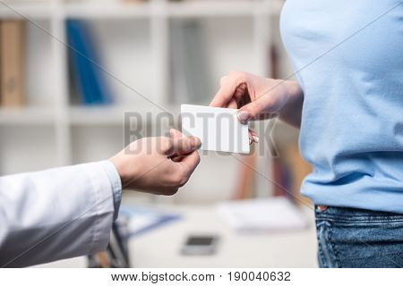 Partial View Of Doctor Giving Blank Card To Patient At Clinic