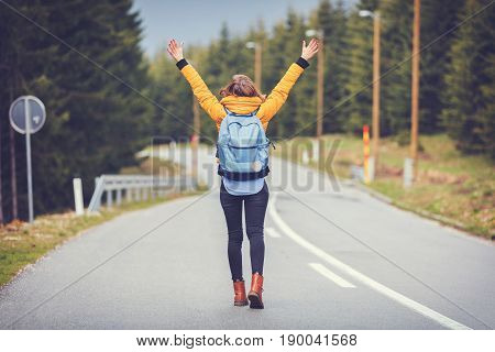 Girl enjoying alone on the road with arms wide open.