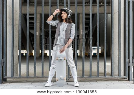 Active girl. Full length portrait of energetic girl is standing with skateboard and touching her cap while looking at camera thoughtfully