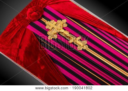 closed coffin covered with color striped cloth decorated with Church gold cross isolated on gray luxury background. Ritual objects for burial. Surrender body dust of the earth. Close-up details.