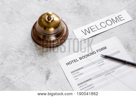 booking form for hotel room reservation, pen and ring on stone table background