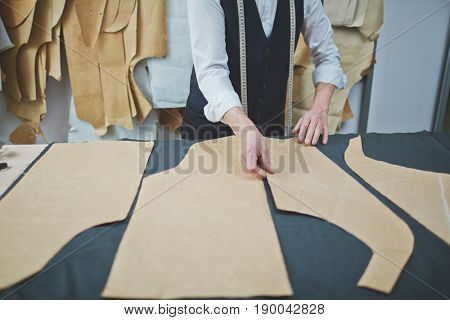 Closeup portrait of experienced old tailor making clothes in atelier shop, laying patterns on fabric