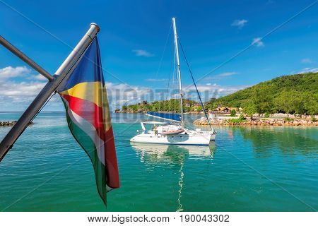White yacht and Seychelles flag at La Digue island