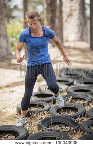 Woman running over the tyre during obstacle course in boot camp