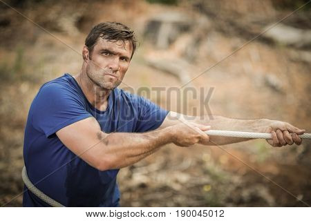 Man playing tug of war during obstacle course in boot camp