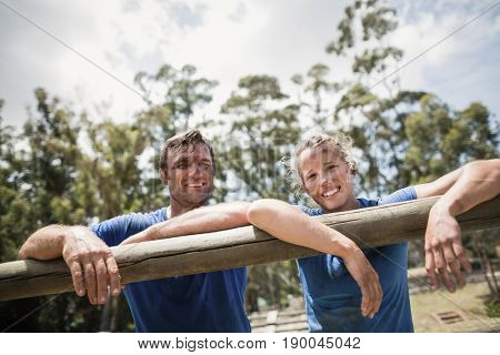 Smiling man and woman leaning on a hurdle during obstacle course in boot camp