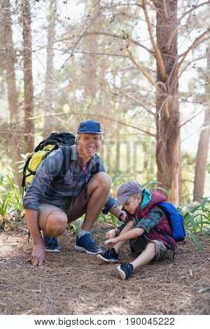 Happy mature father kneeling by boy tying shoelace in forest